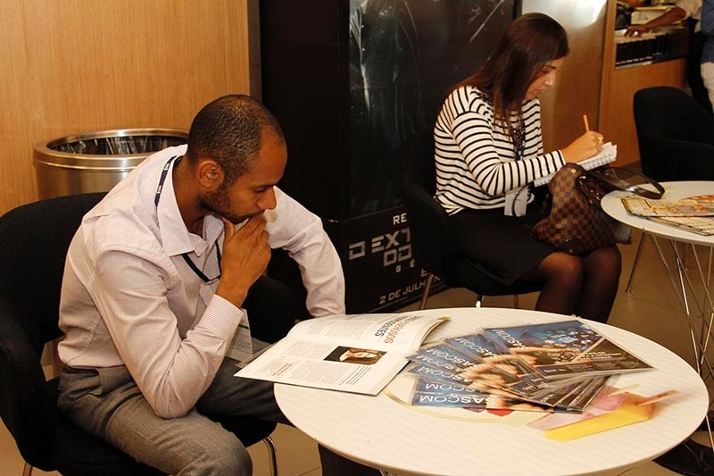 SAS Data Management Forum - Participante lê a revista SASCOM enquanto espera o evento começar.