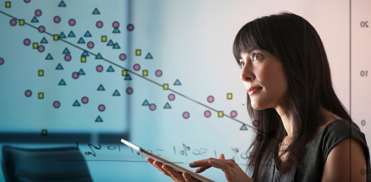 Woman working on tablet with diagram in background