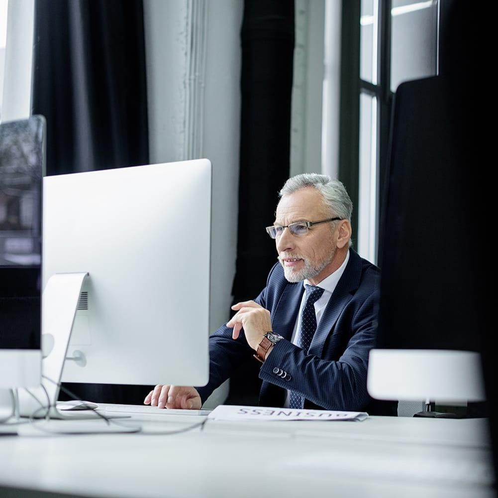 Selective focus of senior businessman working on computer in office