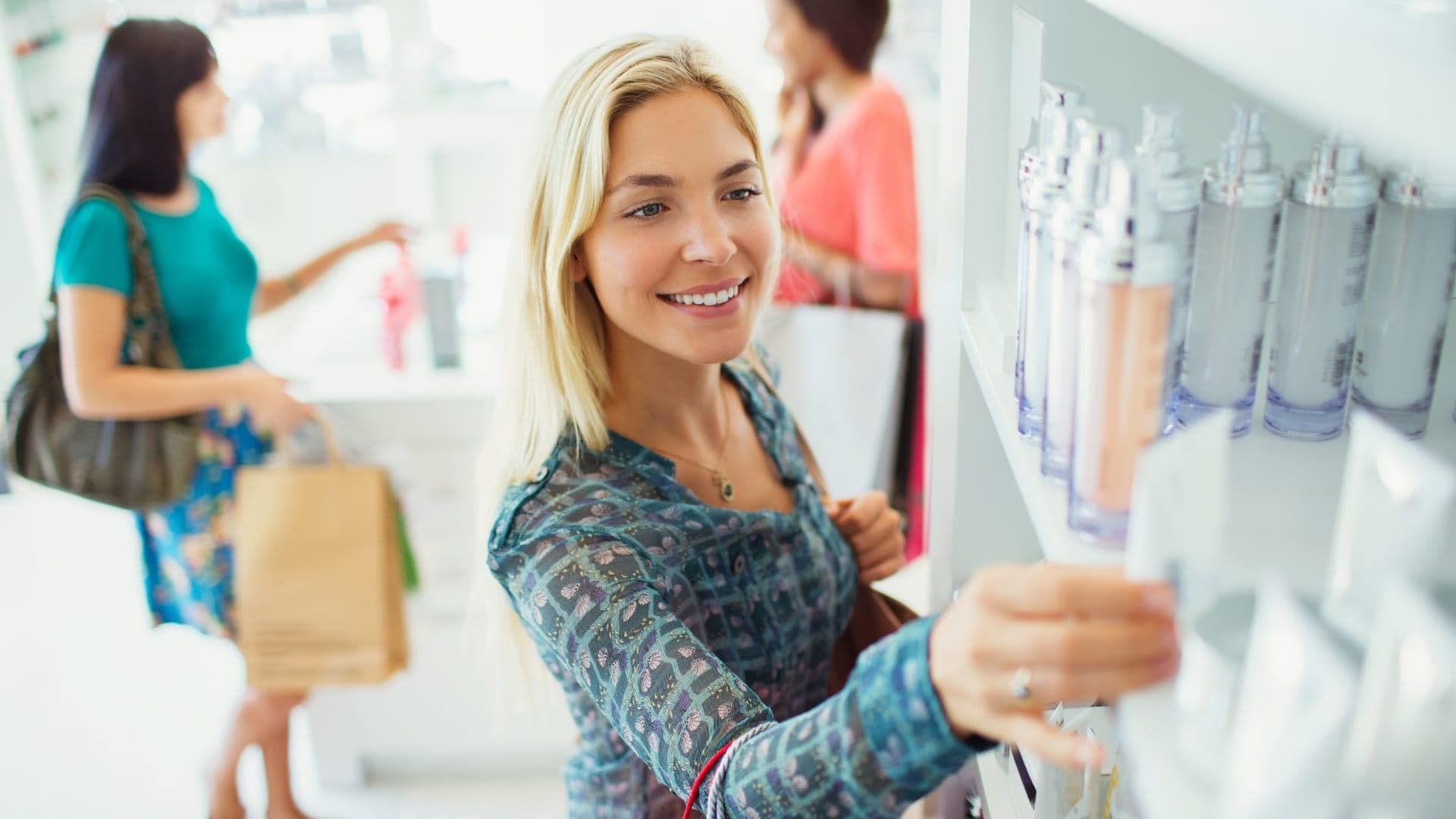 Three young women shopping for skin care products