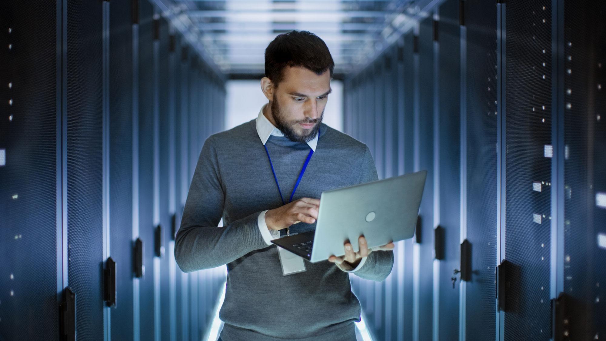 Man holding laptop in data warehouse
