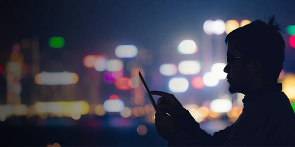 Silhouette of man using tablet device in city