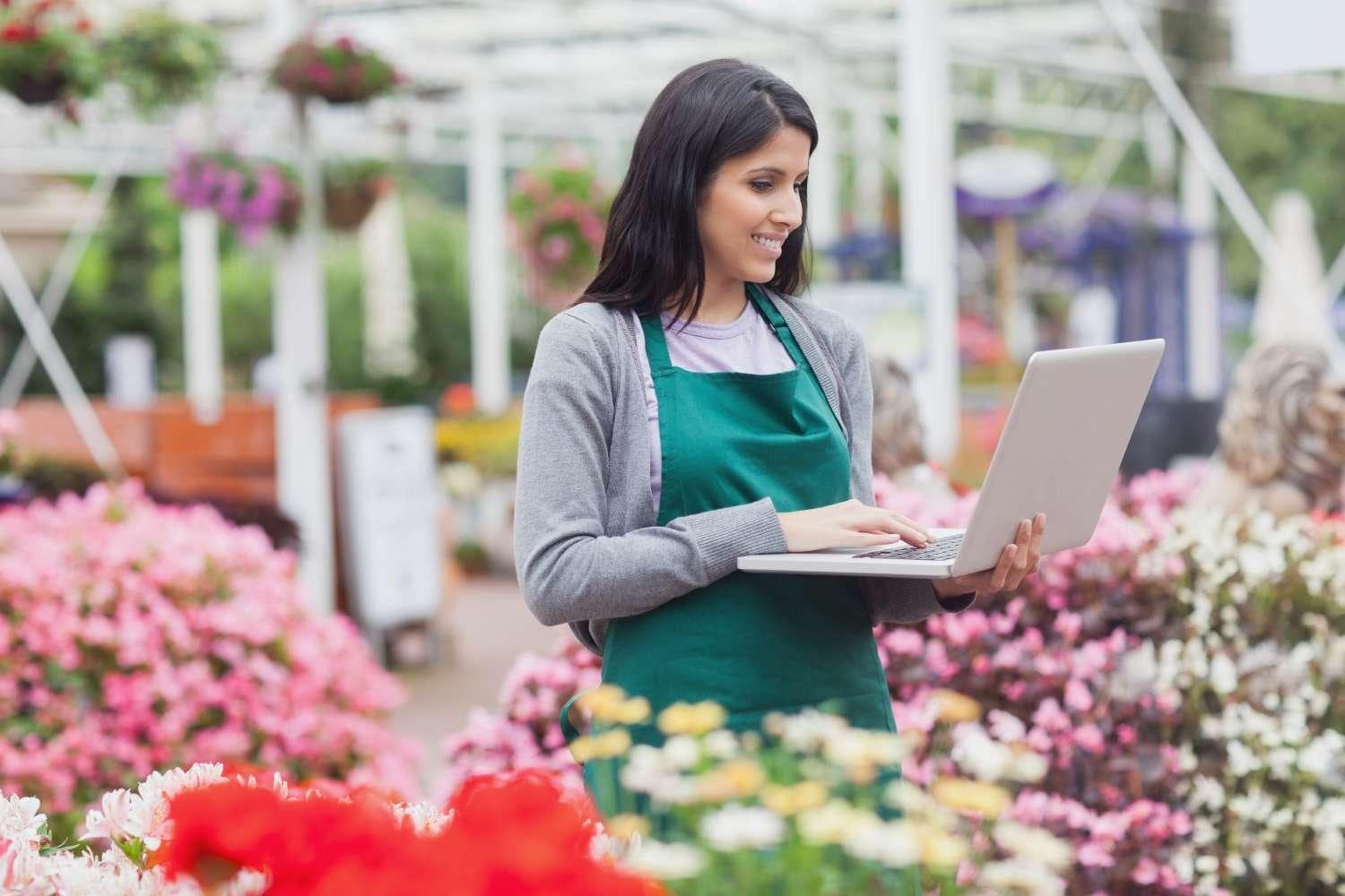 Woman with laptop in flower shop