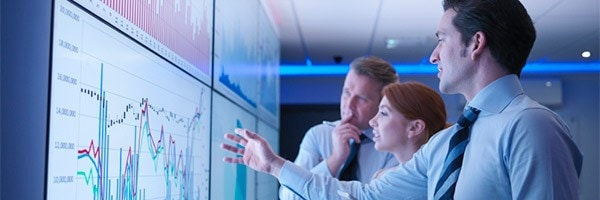 Business-people-discuss-graphs-on-screen