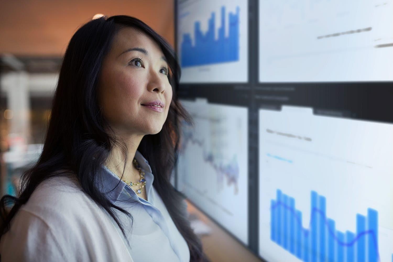 Asian woman views SAS data visualizations on large display