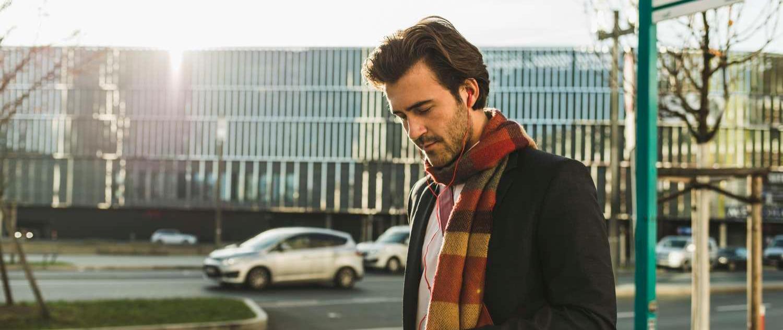 Man wearing scarf looking at phone