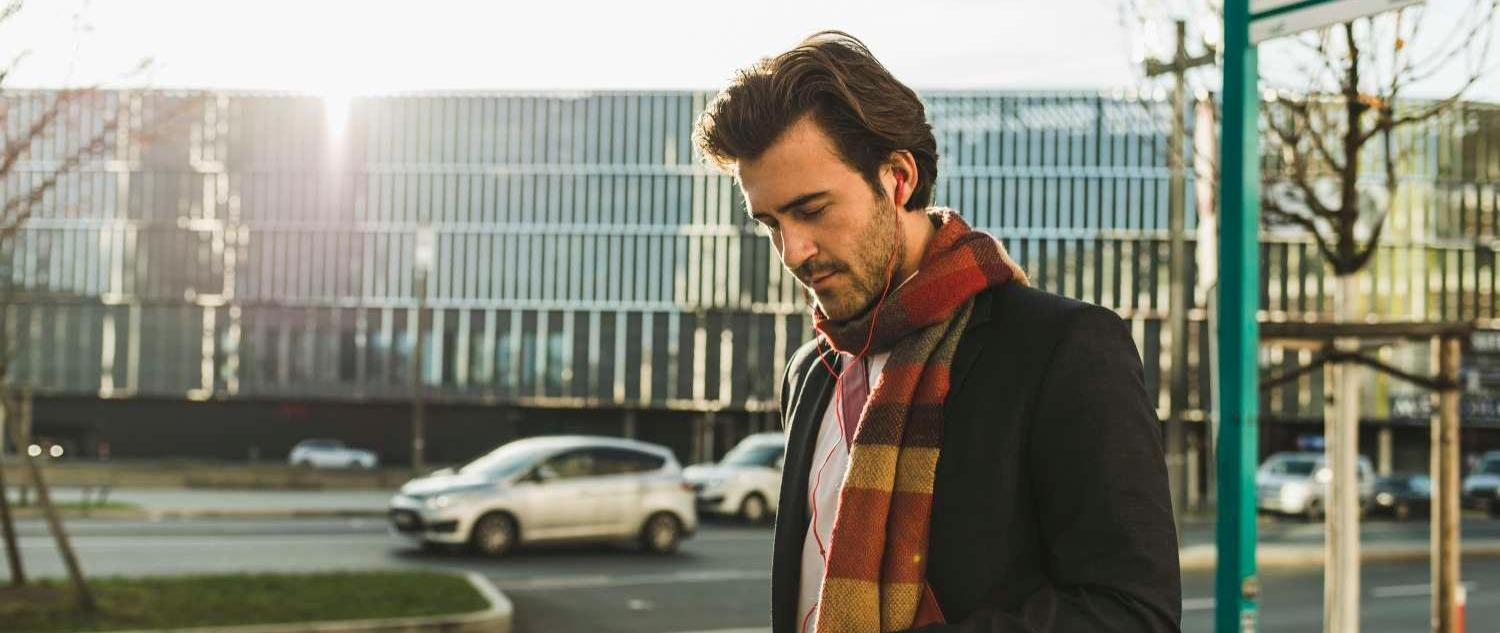 Man wearing scarf looking at phone