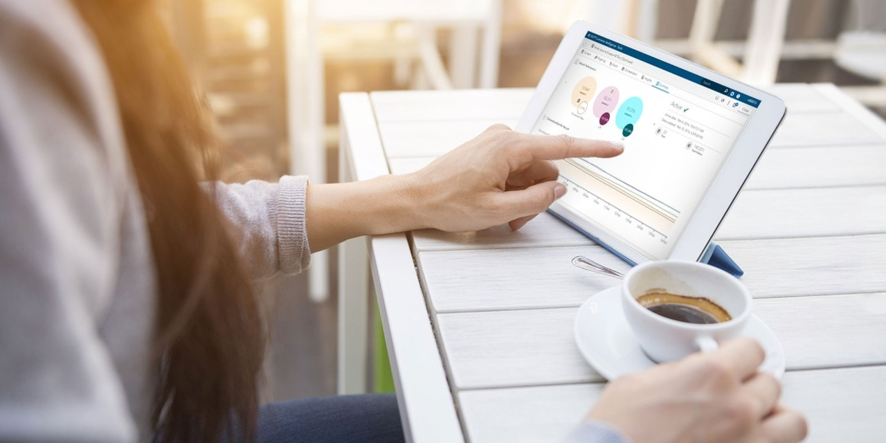 Woman using tablet on table with coffee