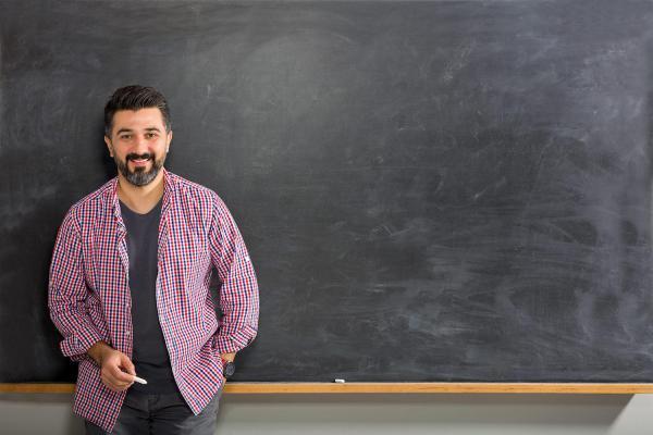 Bearded professor standing at chalkboard