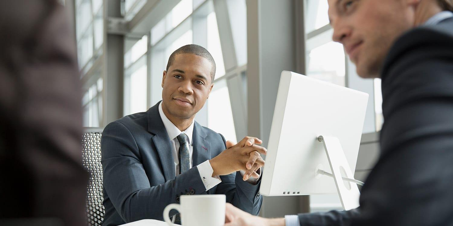 Group of business professionals sitting around computer