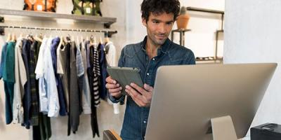 Retail store owner using computer and tablet inside clothing store