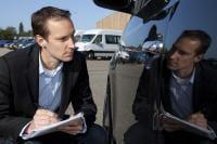 Insurance agent examining car damage