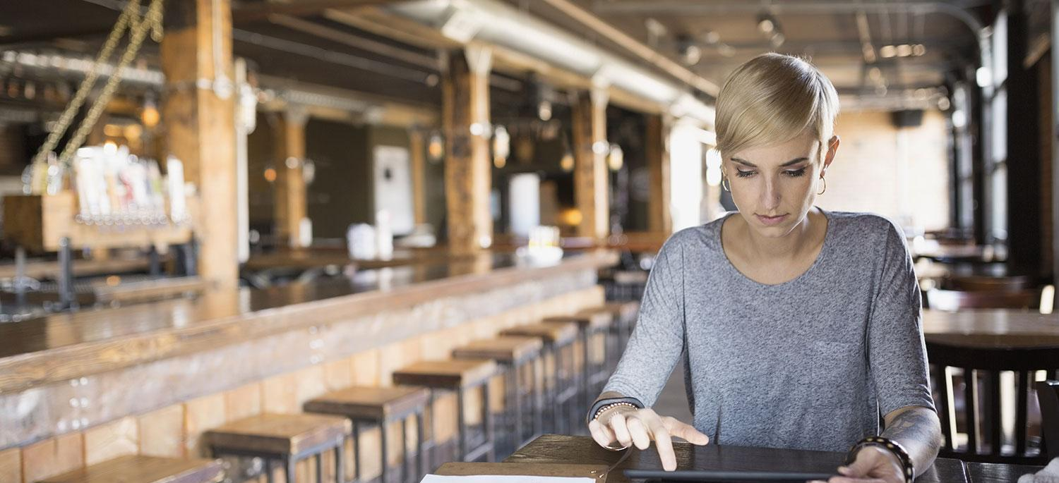 Woman working on a tablet at table