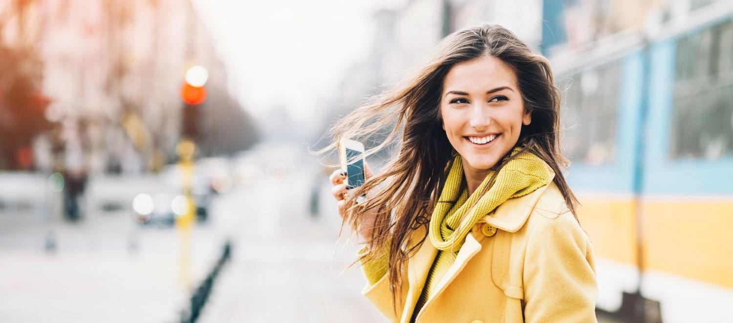 Smiling woman with a phone on street