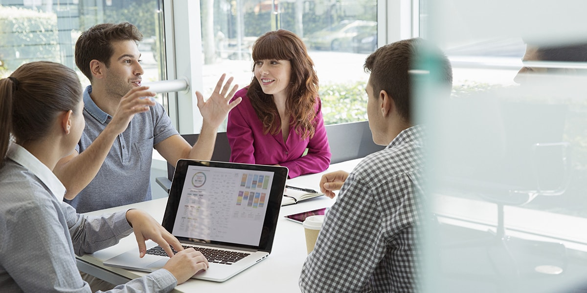 Coworkers in conference room with laptop