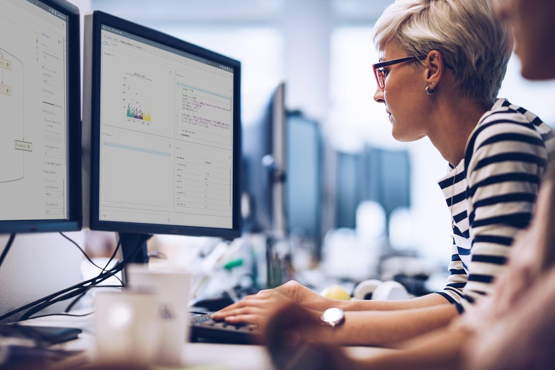 Female data scientist coding with desktop computers