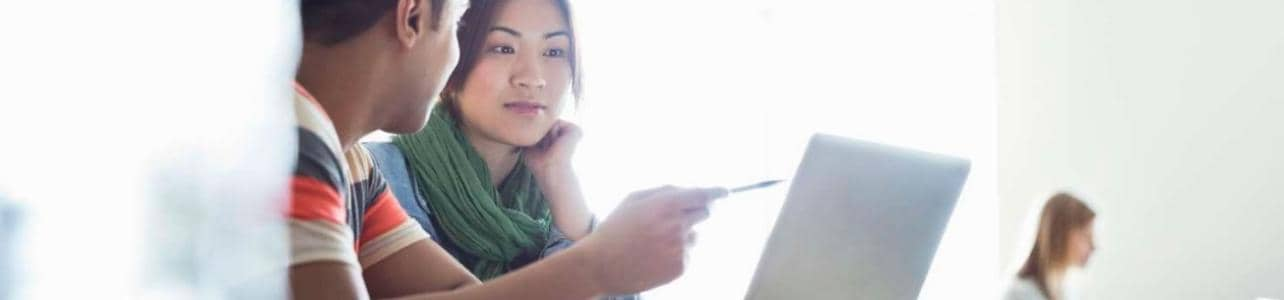 Students using laptops in classroom at college campus