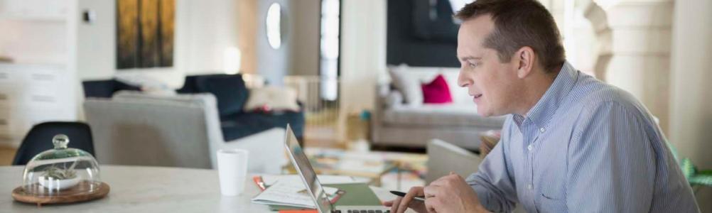 Человек, работающий на ноутбуке за кухонным столом