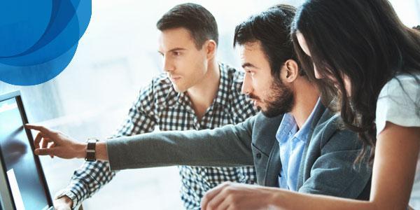 Три человека работают за компьютером