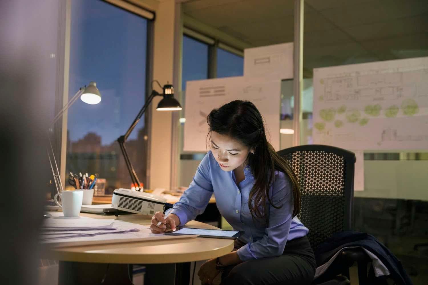 Young asian woman working late in office