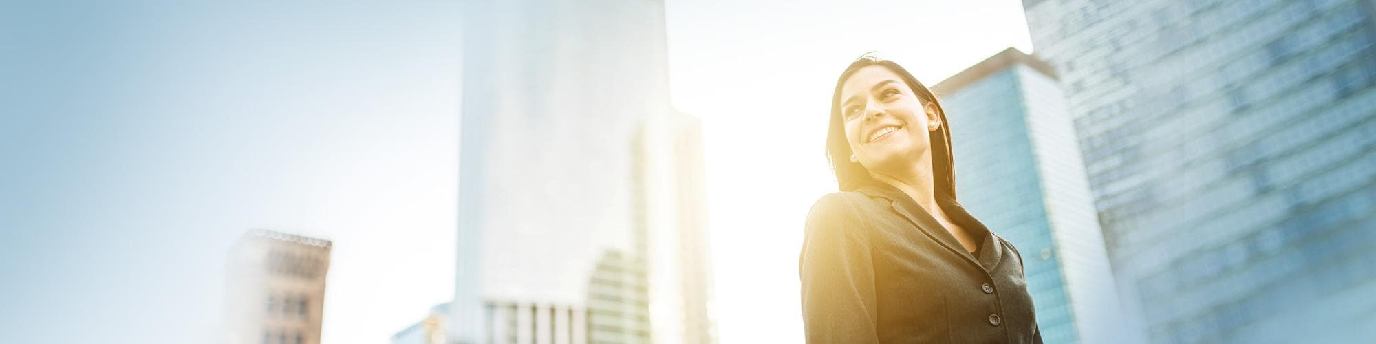 Woman in brown business suit looking up in city