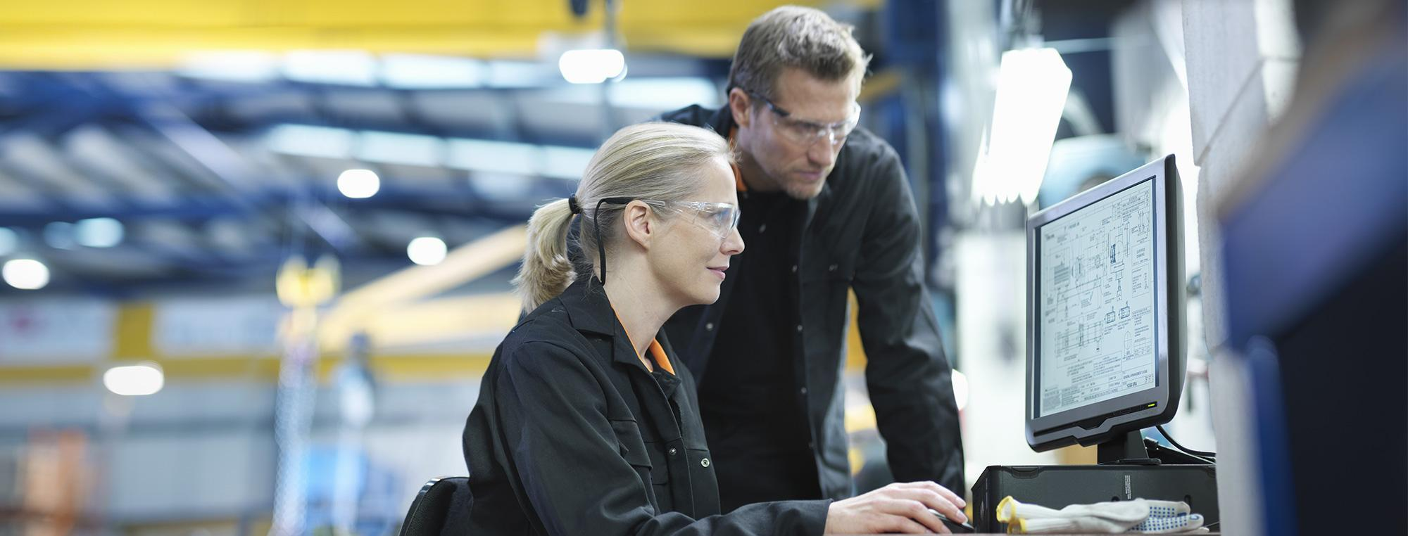 Two manufacturing professionals working on computer on factory floor