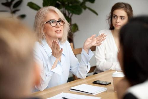 Aged businesswoman, teacher or business coach speaking to young people