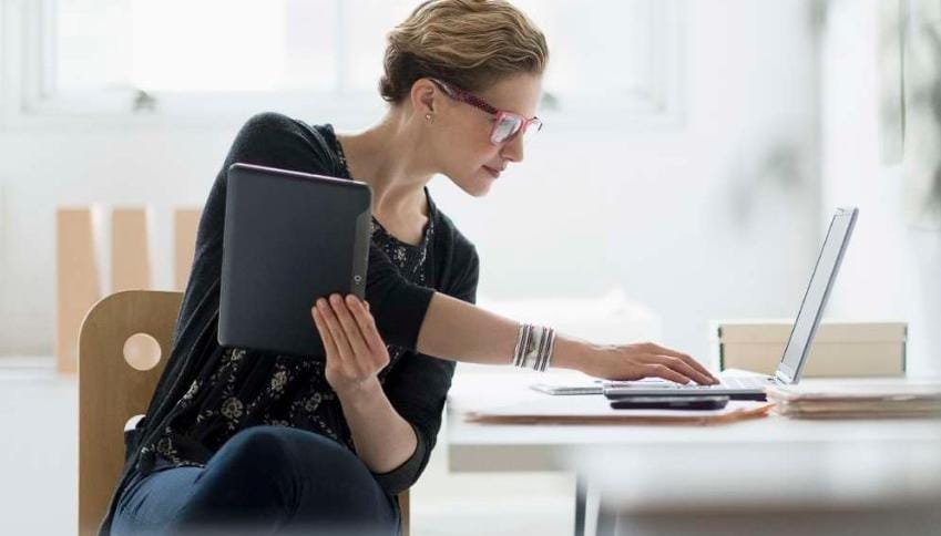 Woman working on laptop and tablet device