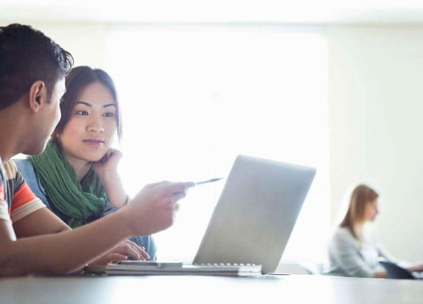 Two people working together on laptop