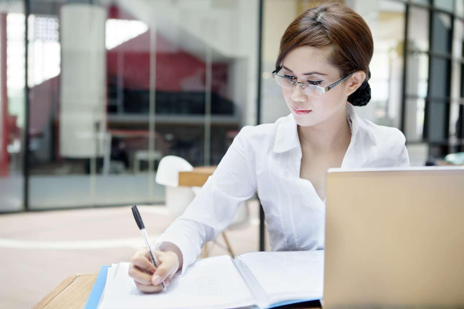 Businesswoman with Laptop writing on Document