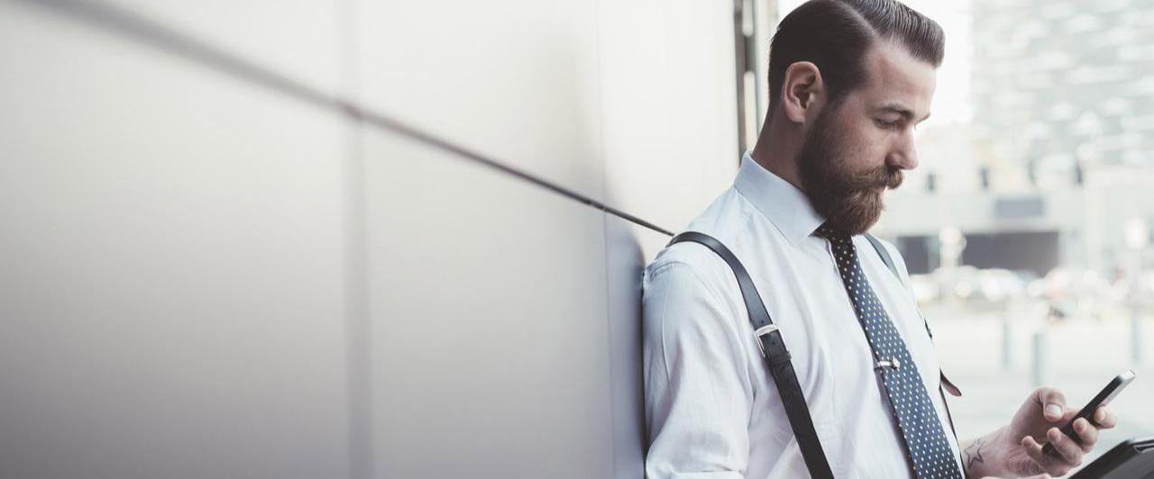 Young businessman leaning on an office wall using smartphone and digital tablet