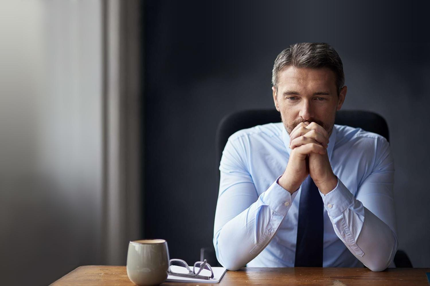 Businessman wearing a tie with elbows on the table