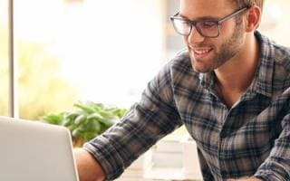 Bearded man in glasses looking at laptop