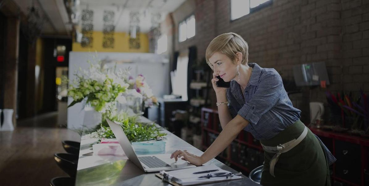 Woman working on laptop and phone inside small business