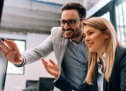 Man and woman smiling sat at a desk