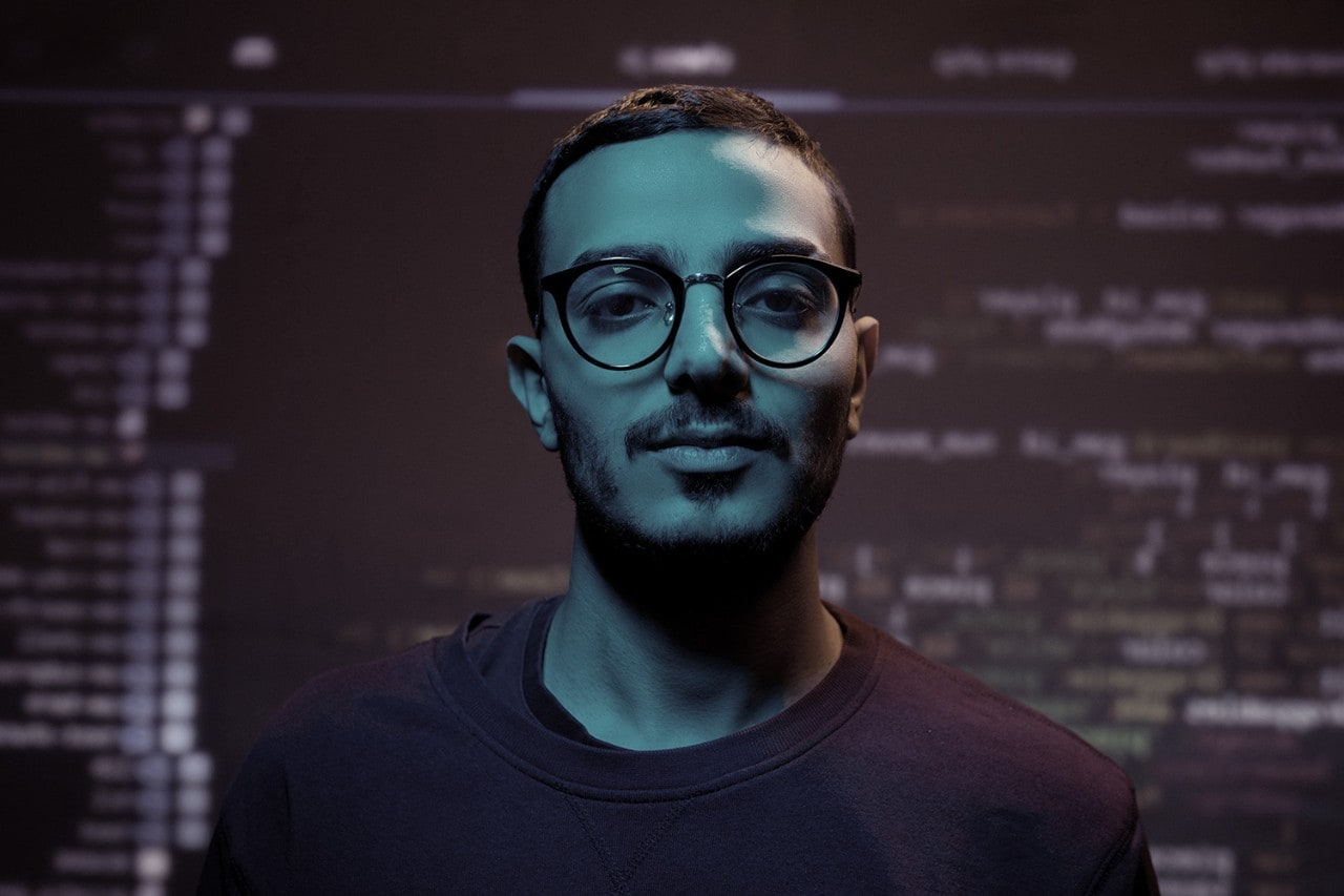 Young Arabian programmer against coding background