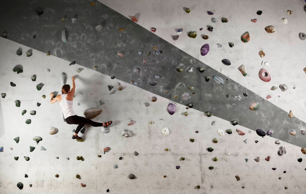Female climber clinging to indoor climbing wall