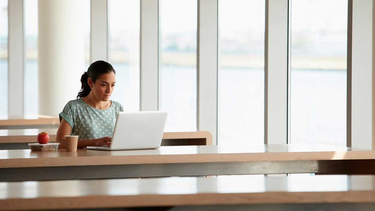 Woman using laptop with packed lunch on desk