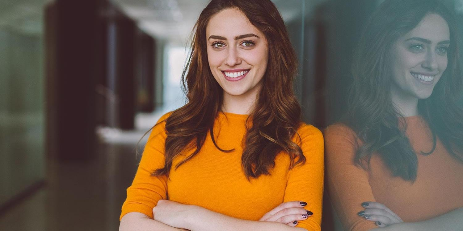 Smiling businesswoman at work - smiling woman in the office looking at camera
