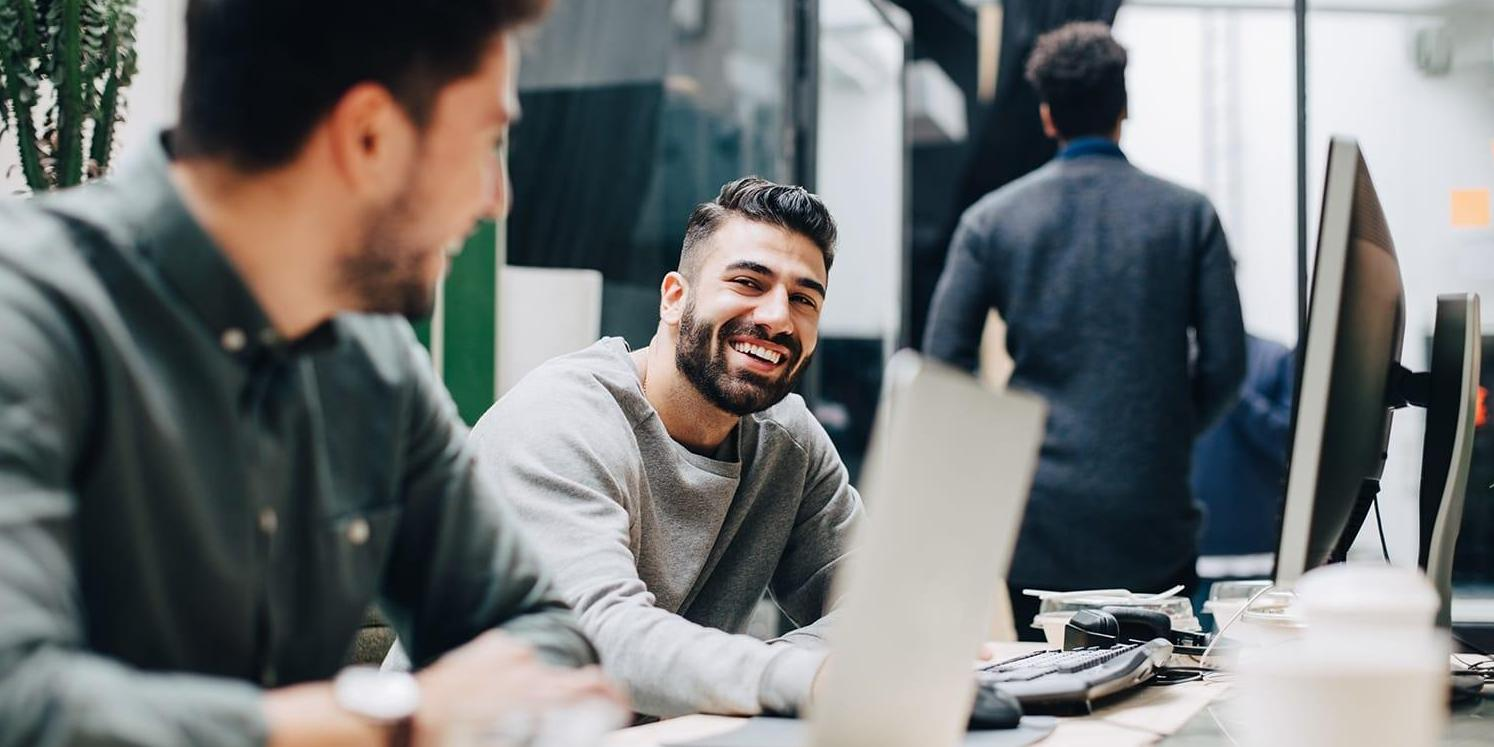 Smiling male colleagues with laptops