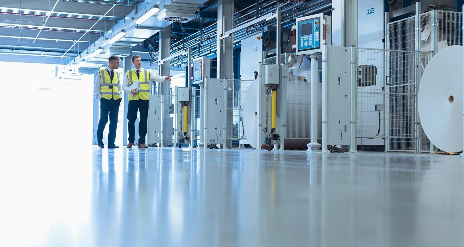 Two coworkers walking through manufacturing facility