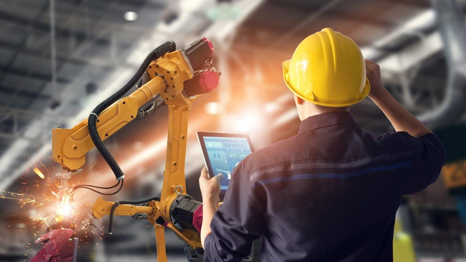 Engineer using tablet to control automation robot