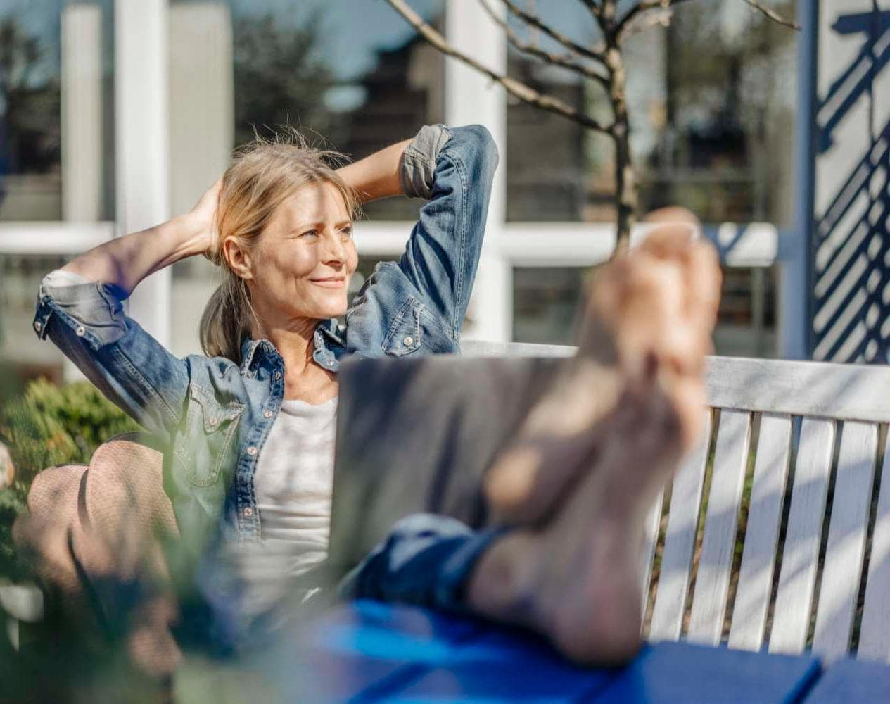 Smiling woman with laptop relaxing outside on garden bench