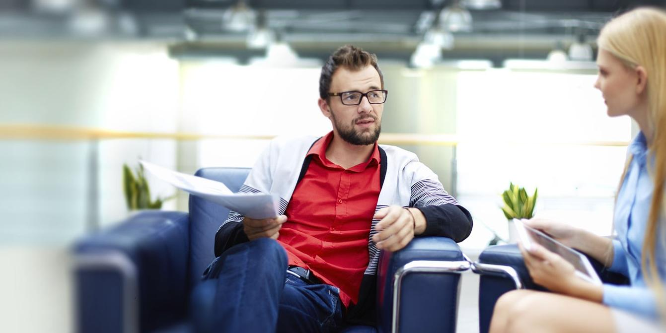 Man with report, woman with laptop, sitting discussing ideas
