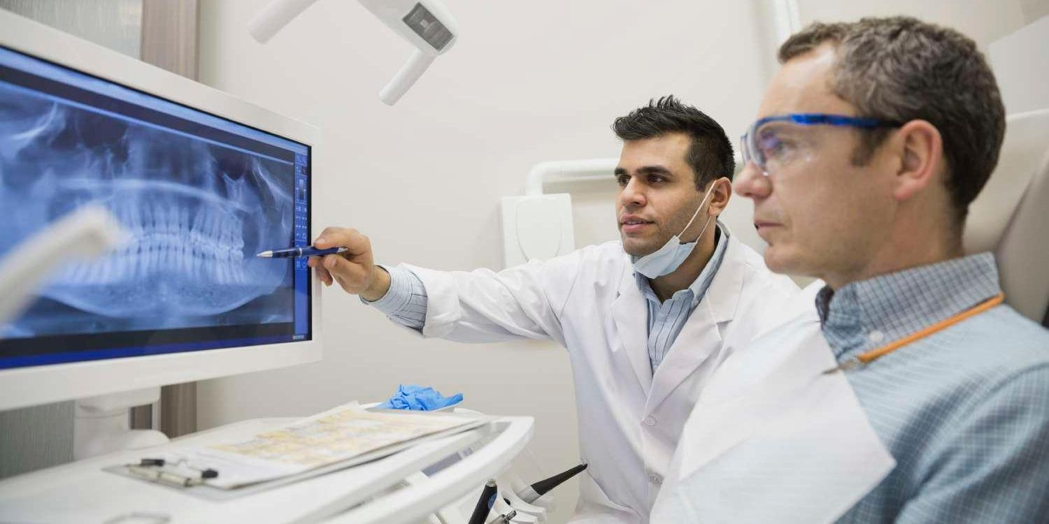 Two professionals studying dental xrays