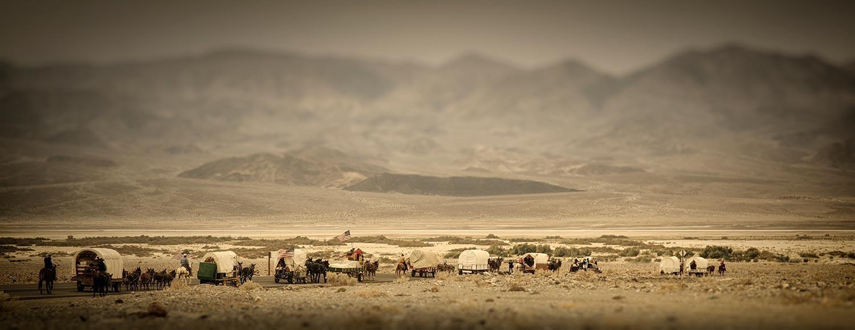 covered wagon train in desert