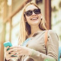 Happy shopping woman looking at mobile phone