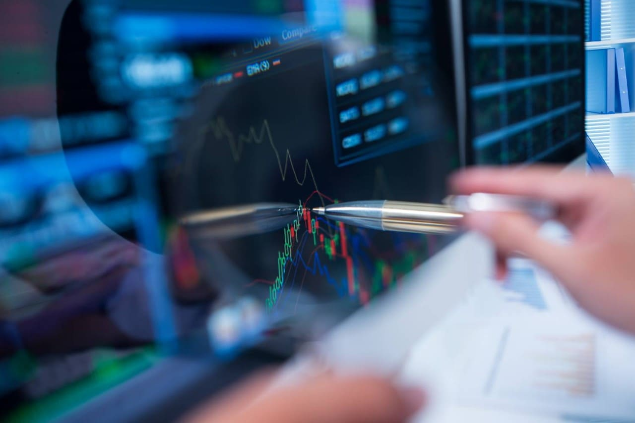 Pen pointing at stock market trading screen