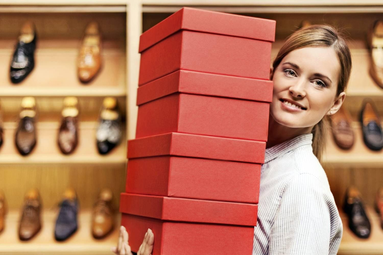 Woman in shoe store holding shoe boxes