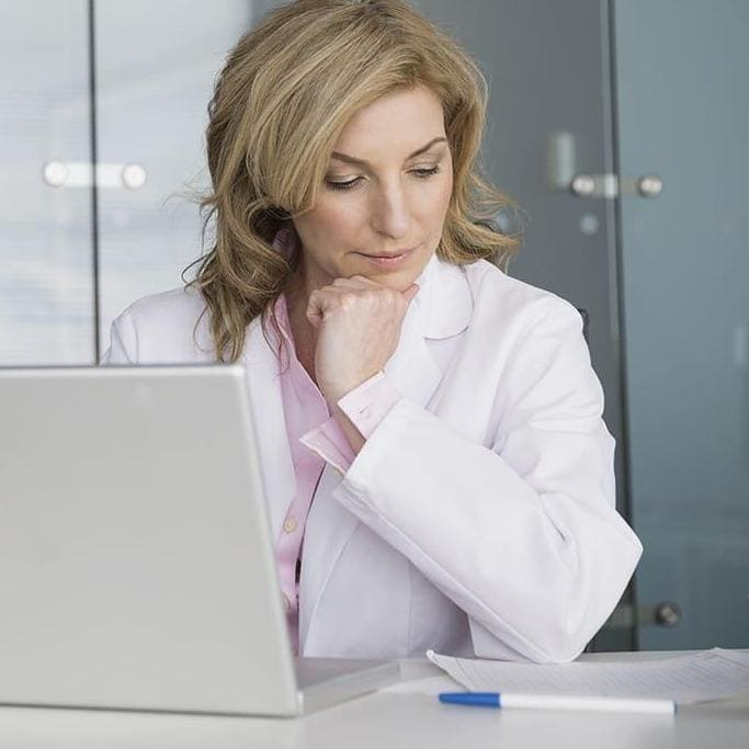 Doctor working at laptop in conference room